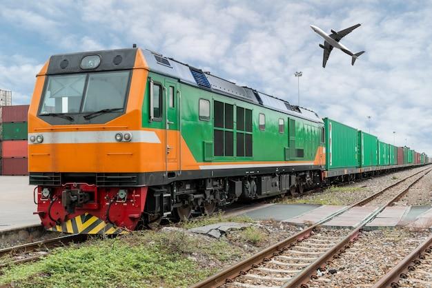 Plataforma de trem de carga com o contentor do trem de carga no depósito com avião de carga no porto