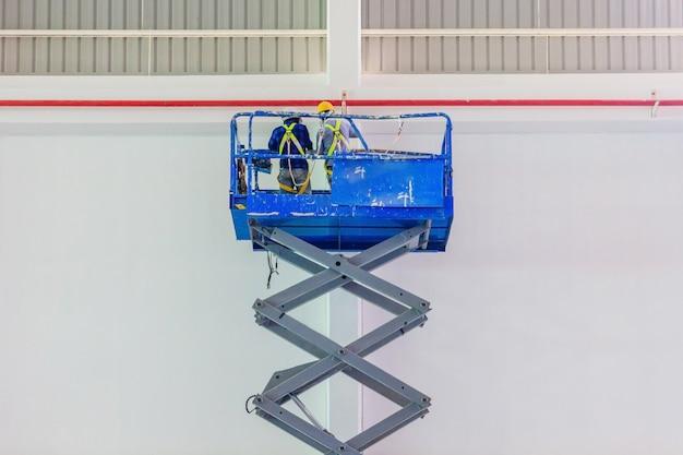 Plataforma elevatória de tesoura com sistema hidráulico elevado em direção a um telhado de fábrica