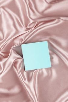 Plataforma quadrada geométrica em fundo de cetim de seda pastel.