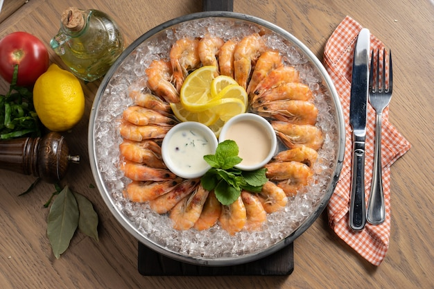 Plateau cozinhou camarão rei resfriado no gelo com limão e molhos
