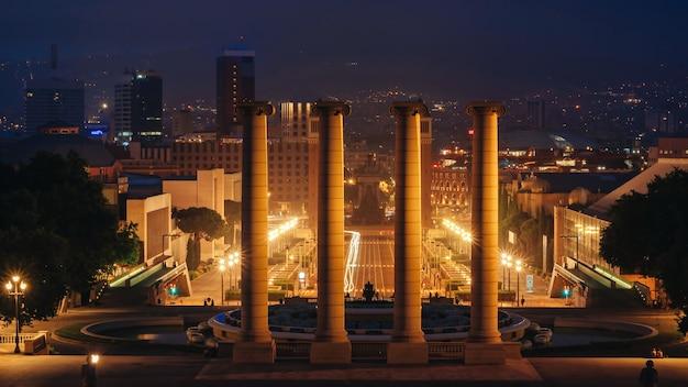 Plaza de espana, a fonte das torres venezianas e as colunas em barcelona, espanha, à noite