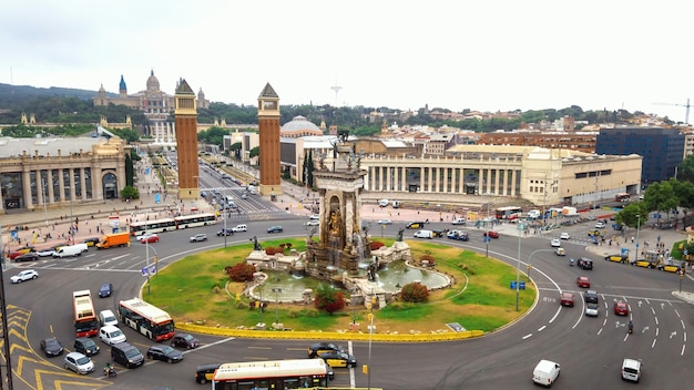 Plaza de espana, the venetian towers e the palau nacional em barcelona, espanha. céu nublado, trânsito