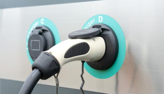 Plugue do carregador de carro elétrico moderno na estação de carregamento ev, energia de combustível verde sem poluição ou tecnologia de veículo híbrido
