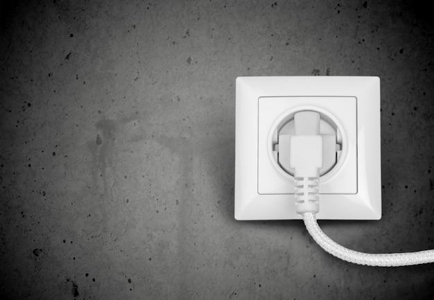 Plugue elétrico branco na tomada elétrica na parede