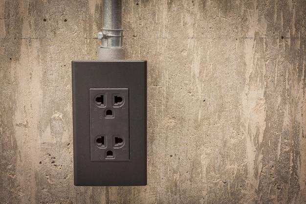 Plugue elétrico na parede de cimento