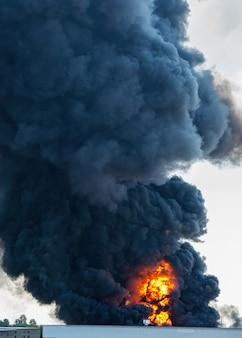 Plumas negras de fumaça de um incêndio industrial tóxico acidental atrás de um prédio de fábrica
