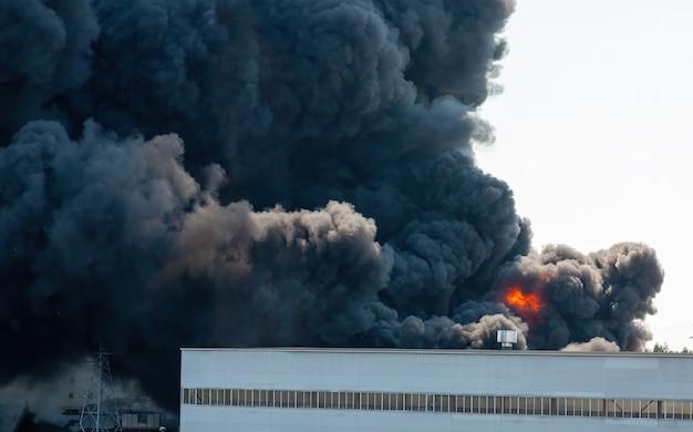 Plumas negras de fumaça de um incêndio industrial tóxico acidental, visto de trás de um prédio de fábrica.