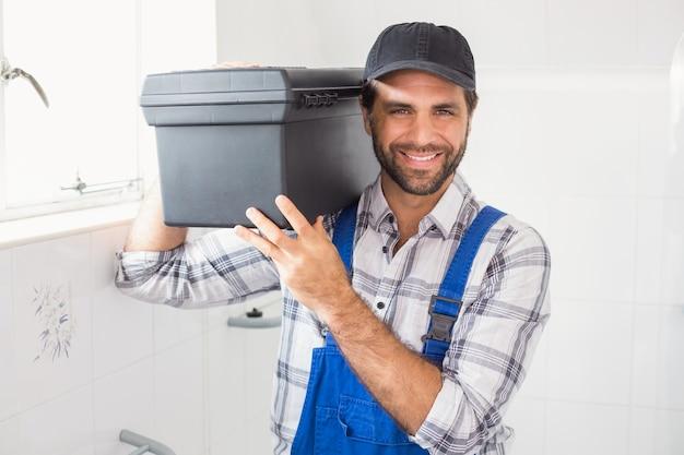 Plumber segurando caixa de ferramentas no ombro