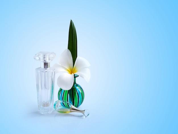 Plumeria branca spa flores em um vaso verde com frasco de perfume de vidro transparente