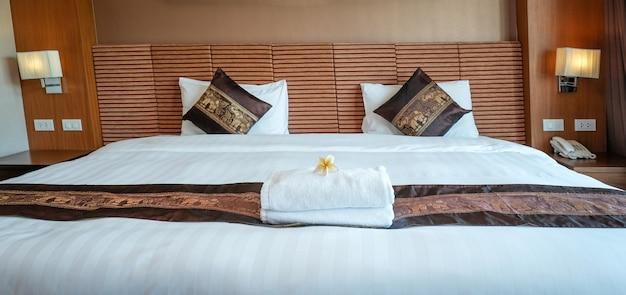 Plumeria e toalhas na cama no quarto de hotel de luxo pronto para viagens turísticas.