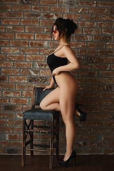 Plus size garota modelo sexy, mulher morena elegante com um busto grande, usando óculos escuros e roupas pretas sensuais, incline-se no banquinho e posando no interior do sotão na frente de uma parede de tijolos