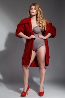 Plus size modelo vestindo lingerie e casaco de malha vermelho