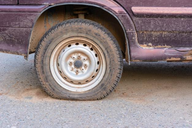 Pneu danificado close-up. a roda do pneu do carro vaza. pneu furado à espera de reparação. carro abandonado no estacionamento.