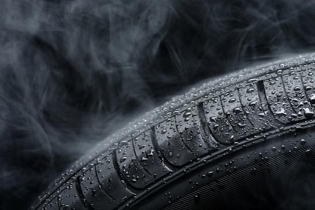 Pneu de carro coberto com gotas de água no meio do nevoeiro