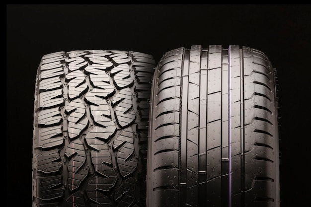 Pneu de lama para picapes e caminhões e um pneu de passageiro lado a lado. close-up de duas rodas, conceito de publicidade em um preto