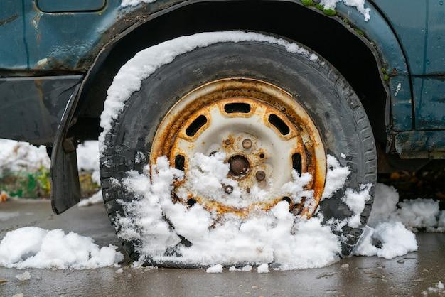 Pneu furado de um carro velho na neve no inverno.