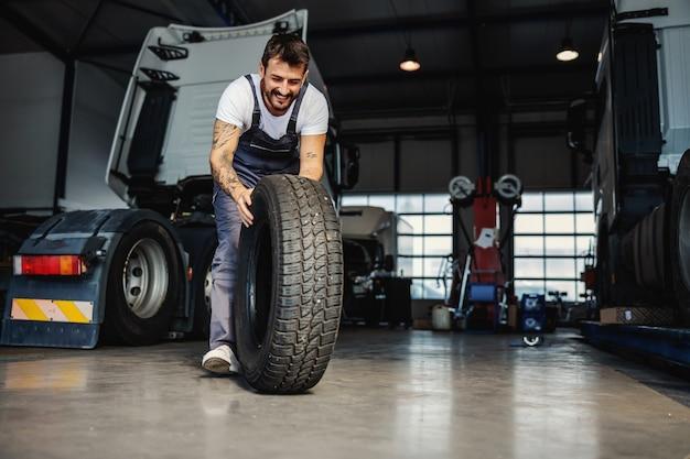 Pneu mecânico trabalhador e sorridente, rolando o pneu para trocá-lo no caminhão