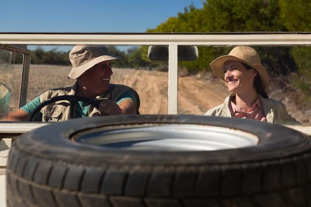 Pneu no capô com sorridente casal sentado em veículo rodoviário