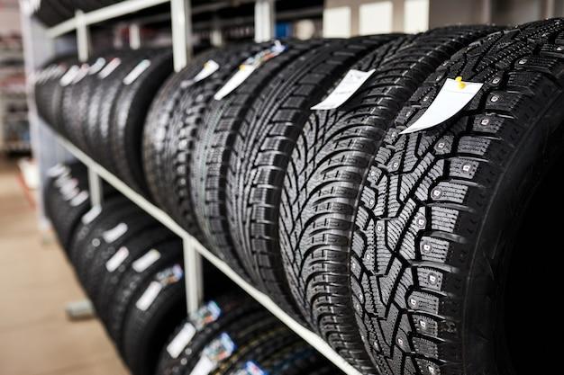 Pneus de automóveis novos e usados na prateleira da loja. foto de close-up de pneus em serviço automotivo