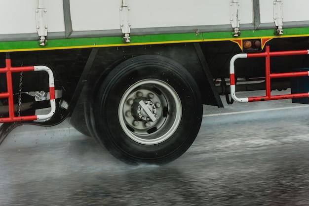 Pneus de caminhão em alta velocidade na estrada enquanto chove