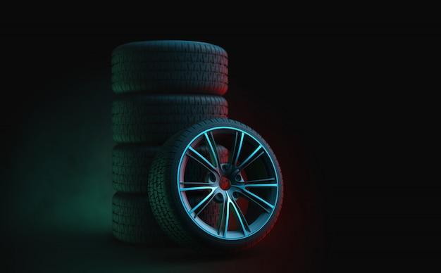 Pneus de carro em pé em um estúdio escuro