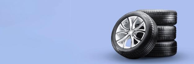 Pneus de verão e pilhas de rodas em fundo azul, novas rodas há muito tempo em branco layout copyspace.