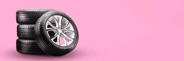 Pneus de verão e pilhas de rodas em fundo rosa, novo layout longo em branco