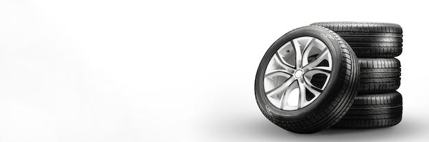 Pneus e rodas de verão empilhados em superfície branca