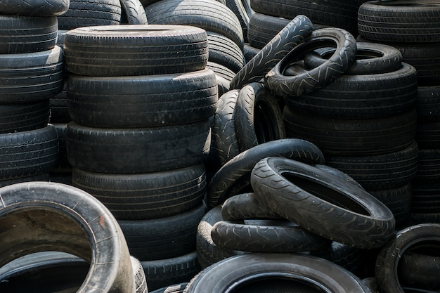 Pneus usados velhos empilhados com pilhas altas