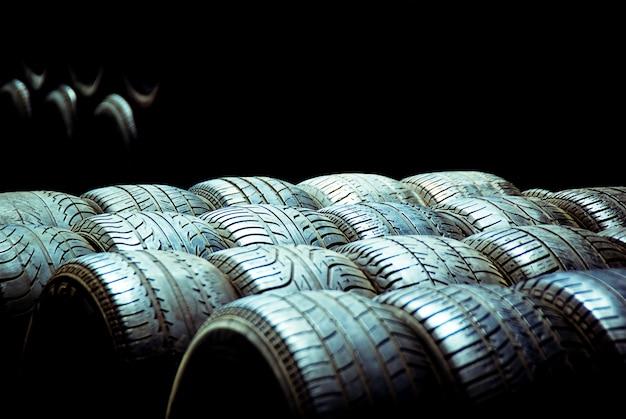 Pneus velhos e rodas de corrida empilhados ao sol