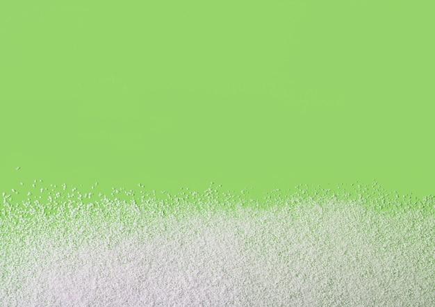 Pó adoçante sem calorias espalhado sobre fundo verde