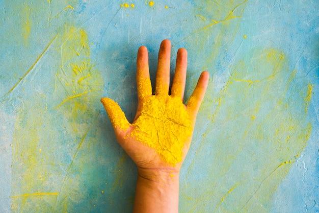 Pó amarelo na palma da mão contra a parede desarrumada pintada com cor