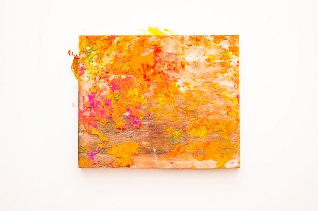 Pó colorido misturado na placa de madeira contra o fundo branco