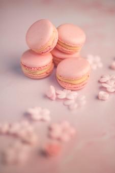 Pó de açúcar polvilhado em macarons azuis com merengue no plano de fundo texturizado preto