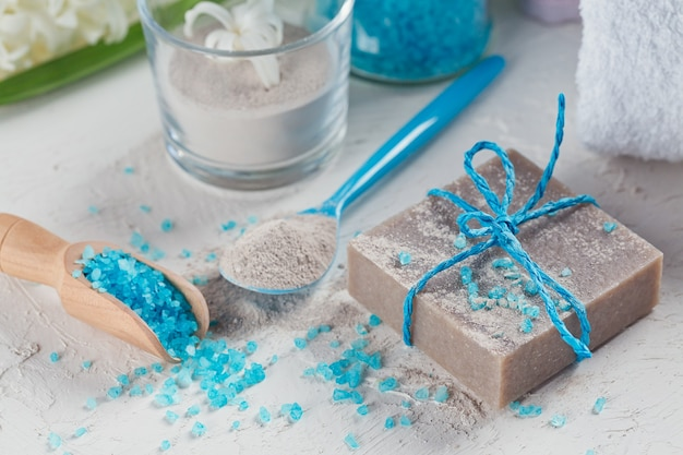 Pó de argila cosmética, sabonete de argila caseiro e sal do mar de banho azul sobre fundo branco. cuidados com o rosto, cuidados com o corpo e conceito de spa.