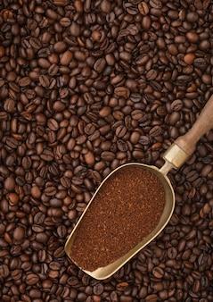 Pó de café torrado fresco em colher de aço vintage em fundo de grãos de café. macro
