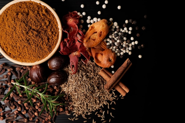 Pó de caril e especiarias em um copo de madeira com fundo preto, conceito da indústria