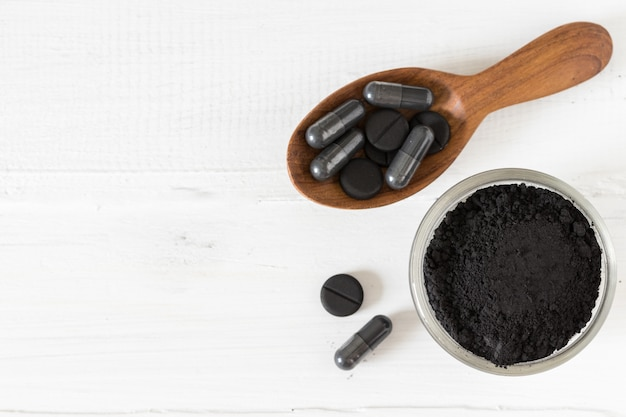 Pó de carvão ativado em uma tigela de vidro e comprimidos em uma colher no fundo branco de madeira
