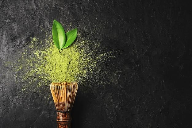 Pó de chá matcha em fundo escuro com batedor e folhas com espaço de cópia.