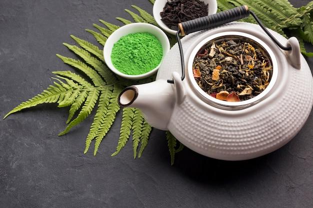 Pó de chá matcha verde e erva seca com bule de cerâmica na superfície preta