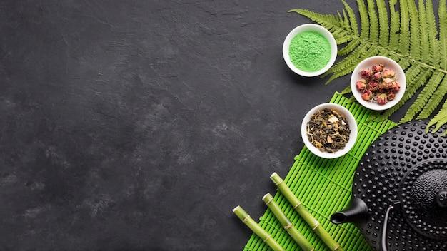 Pó de chá matcha verde e vara de bambu com cópia espaço fundo preto