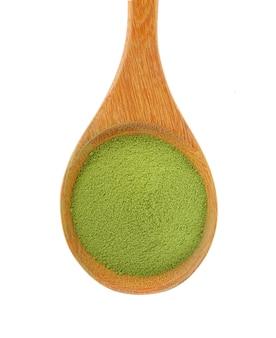 Pó de chá verde em uma colher de pau em uma superfície branca