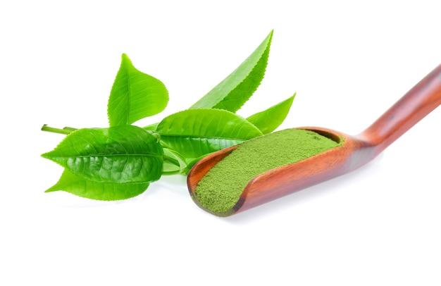 Pó de chá verde em uma colher de pau no fundo branco