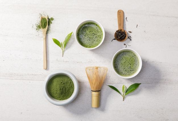 Pó de chá verde matcha orgânico em tigela com batedor de arame e folha de chá verde na mesa de pedra branca
