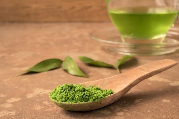 Pó de chá verde na colher de pau em cima da mesa com copo de chá quente