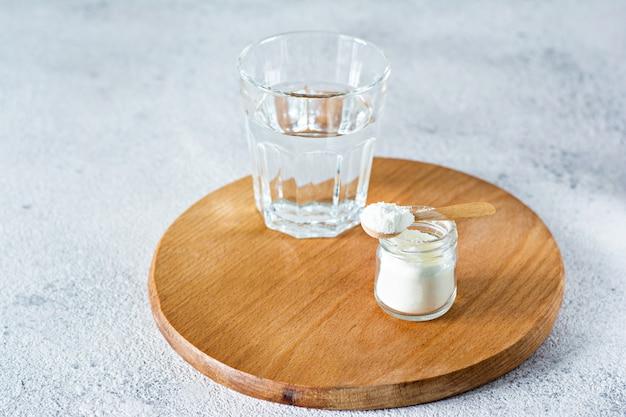 Pó de colágeno com um copo de água sobre um fundo claro. ingestão extra de proteínas. suplemento natural de beleza e saúde para a pele, ossos, articulações e intestinos.