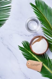 Pó de colágeno em um fundo de mármore da moda com folhas de palmeira verdes. suplemento de beleza natural e saúde, conceito anti-envelhecimento de bem-estar para a pele. vista superior, configuração plana, espaço de cópia