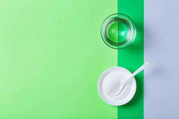 Pó de colágeno em um fundo verde moderno da hortelã. suplemento de beleza natural e saúde, conceito anti-envelhecimento de bem-estar para a pele. vista superior, configuração plana, espaço de cópia