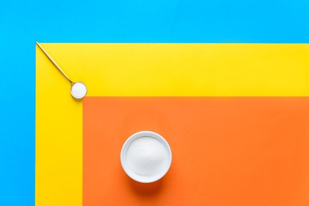 Pó de colágeno marinho em uma tigela branca e uma colher em um fundo colorido. suplemento dietético.