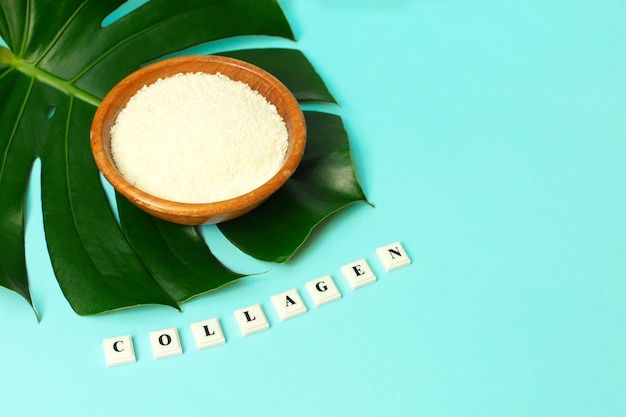 Pó de colágeno na tigela e palavra colageno na folha de palmeira